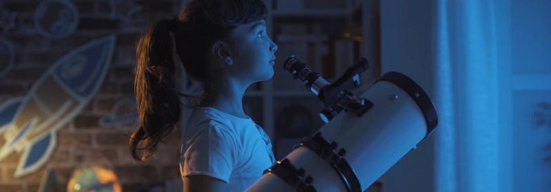 Girl in bedroom with telescope.
