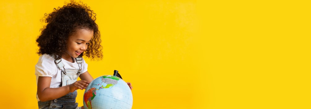 Young girl with globe of world with yellow background.